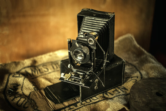 Vintage folding camera with leather accordion, fotokor 1. Photo in retro style.