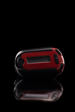 Retro red pager captured isolated on black background and reflective surface