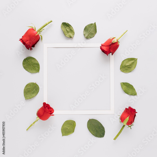 Creative arrangement with green leaves, roses and copy space frame. Minimal nature and Mother's day concept. Flat lay.