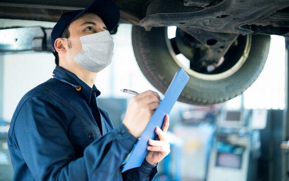 Car mechanic repairing a car, covid coronavirus work concept