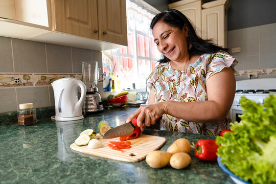 Happy Hispanic Mom Cooking Healthy Food - Mature Woman Cutting Fresh Vegetables In Her Kitchen - Woman Making Healthy Salad