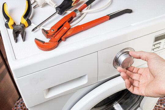 laundry washing machine repair concept. handyman fix washing appliance