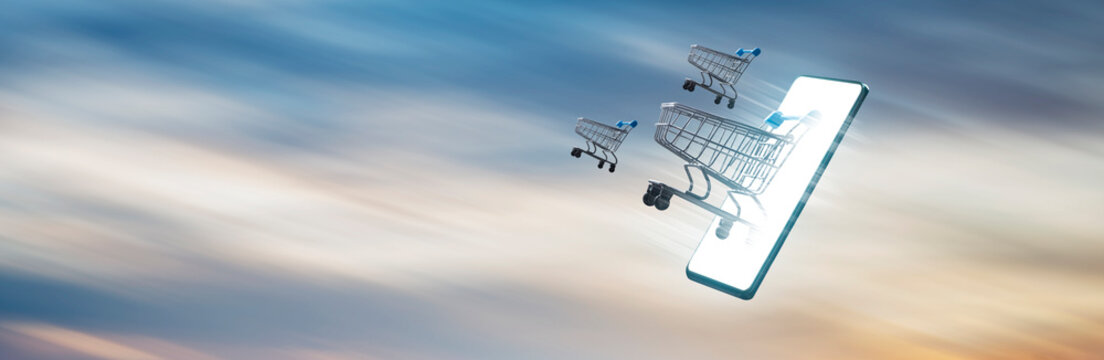 Online shopping concept - shopping carts coming out of a cell phone