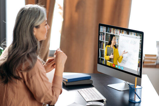Online education. Middle aged gray-haired woman studying online via video call uses app and computer, sitting at her work desk, listens to an online lesson, on the screen the teacher near the