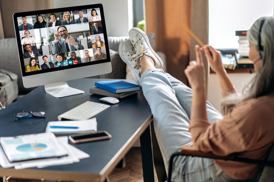 Remote work from home. Modern aged gray-haired woman communicate with coworkers online via video call uses app and computer, sitting at her home office, on the screen many different people