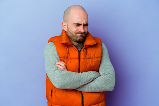 Young caucasian bald man isolated on purple background blows cheeks, has tired expression. Facial expression concept.