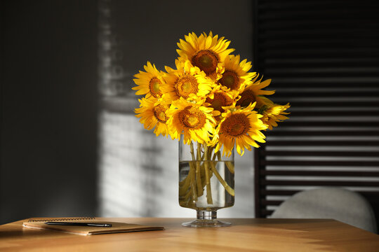 Bouquet of beautiful sunflowers on table in room