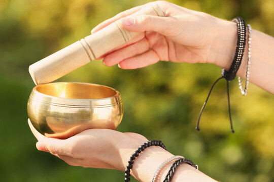 Woman using singing bowl in sound healing therapy outdoors, closeup