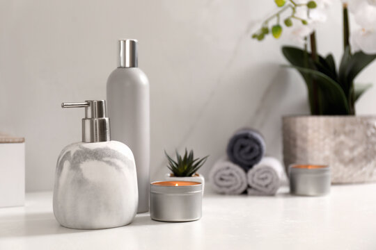 Toiletries and burning candle on countertop in bathroom. Space for text
