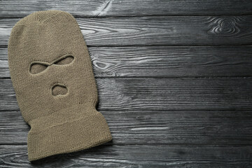 Beige knitted balaclava on black wooden table, top view. Space for text - fototapety na wymiar