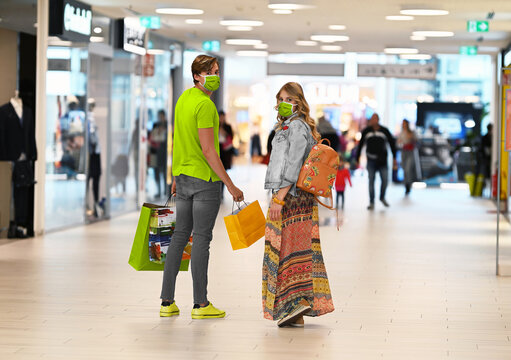 New trendy colors for fashion 2021: yellow and grey. Shopping at the time of Corona Virus or Covid-19. Handsome young and fashion couple at the shop center walking with protective surgical face mask.
