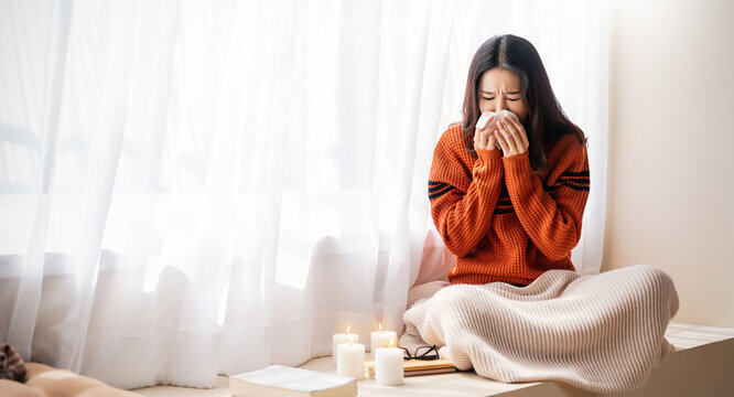 Young asia woman have a cold blowing her runny nose with tissue paper. Portrait of Asian beautiful girl get sick sneezing from flu in her office. Healthcare medical overload burnout, winter concept