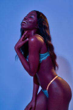 Joyful african american young female model with gorgeous body laughing while posing in sexy lace lingerie isolated in neon uv purple blue light