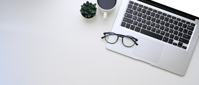 Horizontal photo of computer laptop, glasses, coffee cup and copy space on white background.