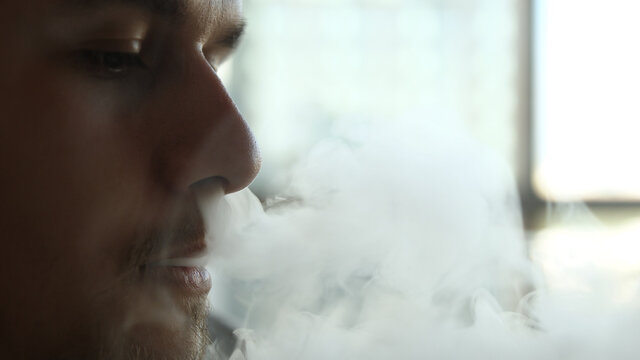 Close-up of man inhaling an e-cigarette vaping device. slow motion