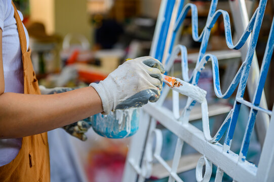 Painter woman painting for house improvement when lock down during Covid-19.