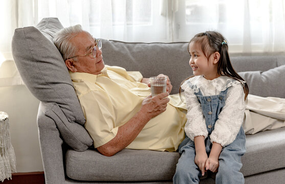 Grandfather and granddaughter togetherness at home. Retirement age lifestyle with family on holiday.