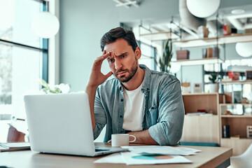 Fototapeta Thoughtful businessman looking at laptop screen