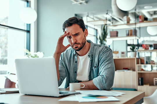 Thoughtful businessman looking at laptop screen