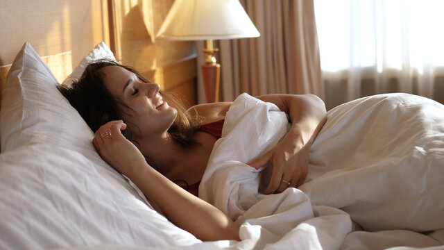 Calm young woman in comfortable cozy fresh bed enjoying healthy good sleep nap