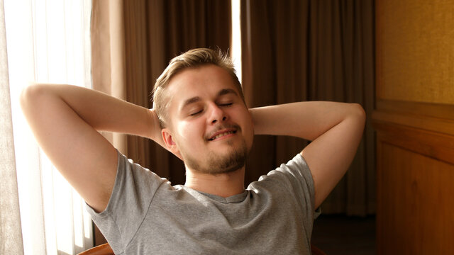 Happy lazy young hansome man relax daydream meditate sit on comfortable sofa at home in living room