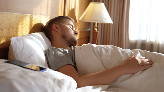 Young man sleeping while phone lying on a pilow in bed