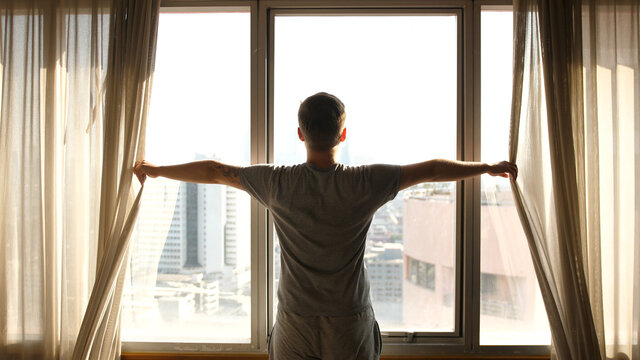 Man Opening the Window Curtain on a Sunny Morning in a Hotel Room, a Man Looking on the Window Relaxed.