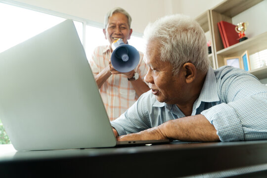 Old Asian elderly yell to a megaphone to talk with a friend for communication. Concept of communication problem in aging cause of ear be without hearing, deaf