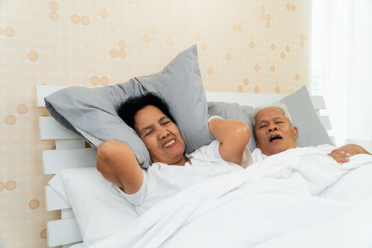 Older Asian woman laying open her eyes and Cover ears with her pillow in bed beside her husband who snores and Makes noise, Marital problems.