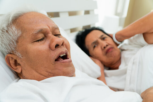 Older Asian woman laying open her eyes and Cover ears with her hands in bed beside her husband who snores and Makes noise, Marital problems.