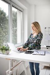 Fototapeta Businesswoman working at ergonomic standing desk.
