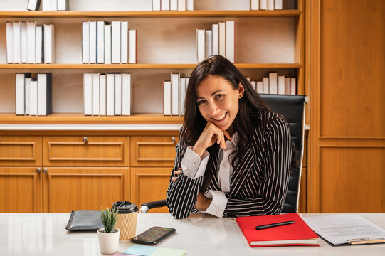 A young businesswoman or lawyer sitting at her desk in the office in front of a bookshelf smiling and looking at the camera.