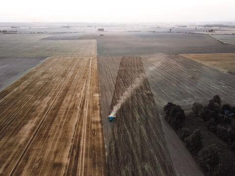 Aerial view of blue tractor working in the farmland ir Lithuania