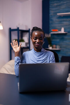 African woman waving at laptop webcam in the course of video conference working late at night from home office. Black freelancer working with remotely team chatting virtual online conference.