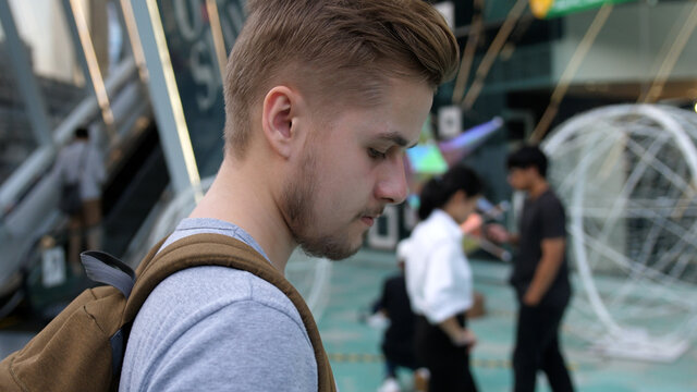Handsome young businessman text messaging on cell phone while walking down city street with backpack. Man looking forward and away thoughtfully. 3840x2160, 4k