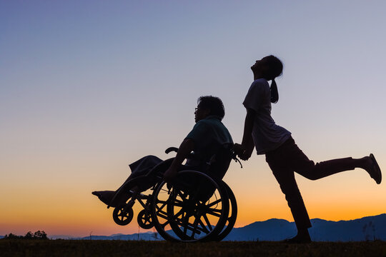Silhouette Disabled handicapped young man in wheelchair walking with his care helper in sunset.