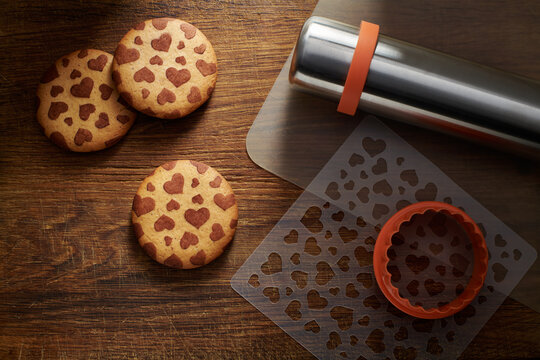 Сookies with a pattern in the shape of hearts, cookie cutter, stencil, baking mat, rolling pin on a brown wooden surface
