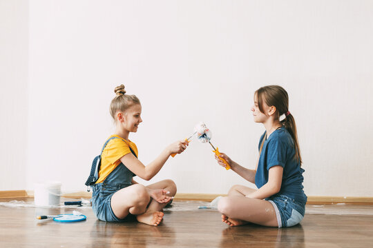 A girl with her sister in bright blue and yellow clothes helps to paint the walls in her room white