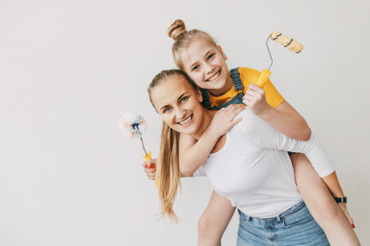 Beautiful and happy mom and daughter paint the walls in the apartment white, laugh and indulge