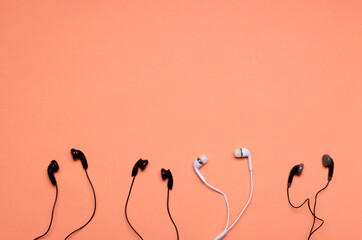 Top view of many earphones on the orange surface.Concept of rooms of audio chats.Empty space