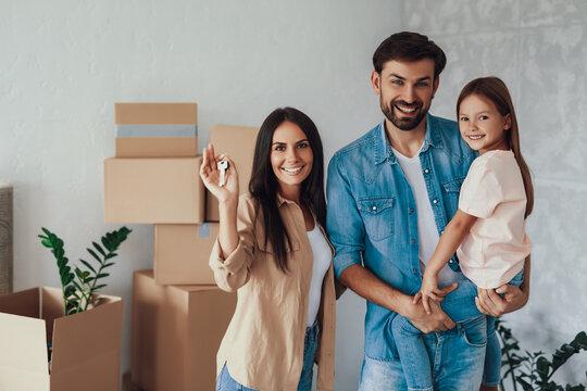 Lovely family of three people looking happy in new home