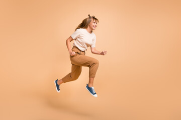 Wall Mural - Full length profile photo of lady jump run wear t-shirt pants sneakers isolated beige color background