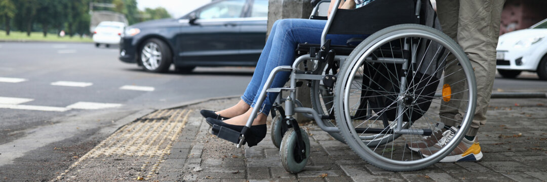 Female legs in wheelchair close up. Help for people with physical disabilities. Man drive wheelchair and stand at pedestrian crossing. Social services for population.