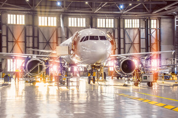 Large-scale inspection of all aircraft systems in the aircraft hangar by worker mechanics and other specialists. Bright light outside the garage door. Wall mural