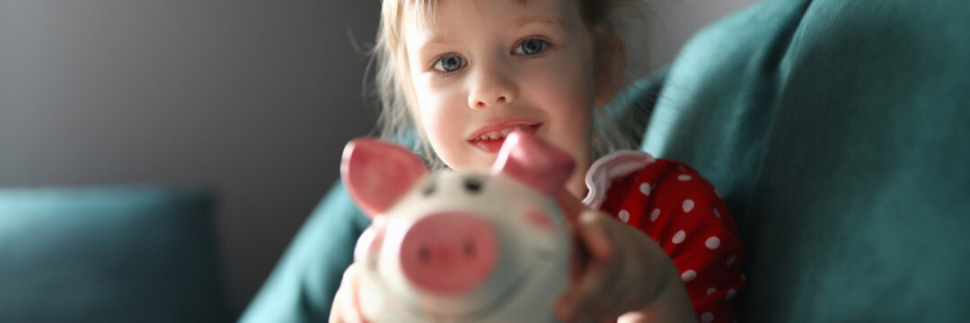 Girl in red dress with polka dots sit on couch and smile. Child hold pink piggy bank in her hands and show. Savings and accumulation of funds. Teaching thrift children.