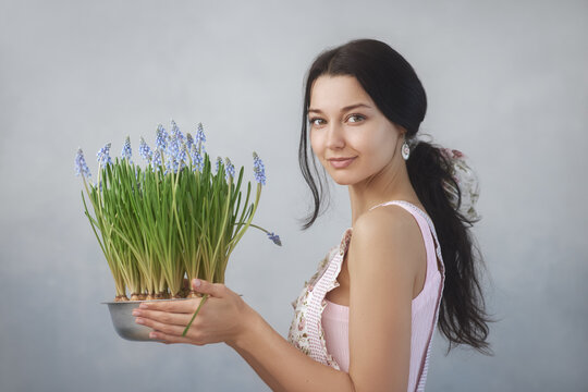 Woman Holding Bouquet of Flowers in Hands Indoors