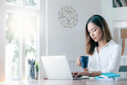 Young attractive asian woman holding mug and working on laptop at home, work from home concept.
