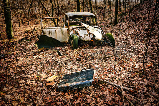 Car wreck desolated worn and rusty left in a forest, Denmark