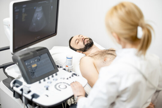 Doctor examining liver of male patient with ultrasound scan in medical clinic. Health and wellness concept.