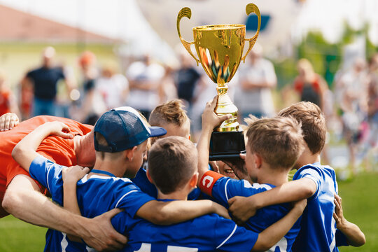 Boys sport team celebrating success with young coach. Team captain rising golden trophy with teammates. Happiness in school football team after winning tournament final game. Kids cheering in group